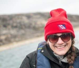 Lacey poses in sunglasses and red hat in front of a lake