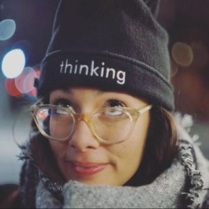 "Soley looks up through glasses at her beanie hat which has the work ""thinking"" embroidered on it."